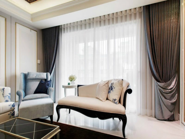 Маленький диван на фоне большого окна в зале