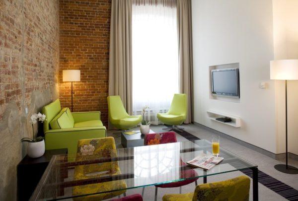 Стеклянный столик и зелёный диван в интерьере