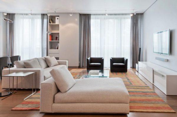 Бежевые диваны в гостиной с двумя окнами