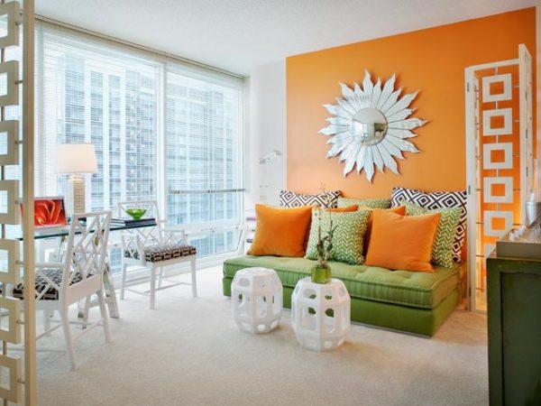Зелёный диван с оранжевыми подушками