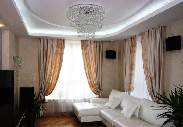 Белый коженый диван в гостиной с двумя окнами